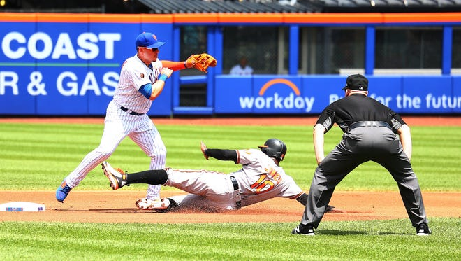 Baltimore Orioles center fielder Adam Jones (10) is forced out at second base  by New York Mets second baseman Asdrubal Cabrera (13) on the first end of a double play during the first inning at Citi Field.