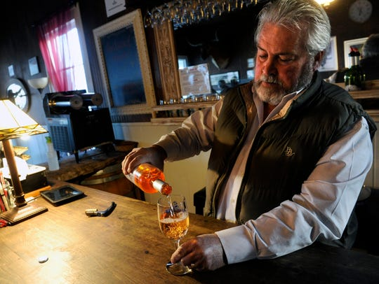 Adrian Allen pours a glass of wine for a customer Thursday at Blue Duck Winery in Albany.