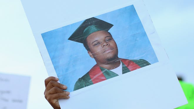 A demonstrator carries a picture of Michael Brown, 18.