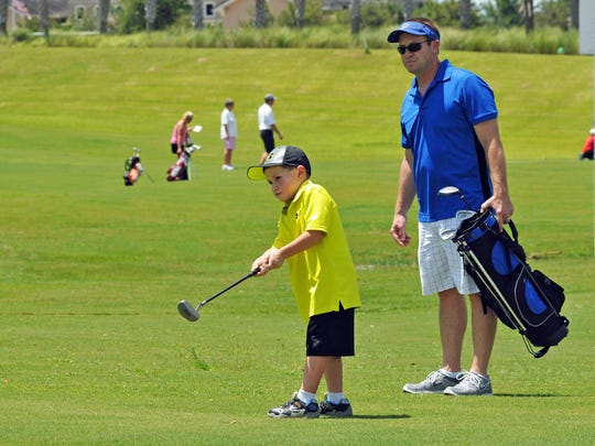 Greyson Steele, age four, and his dad, Chris Steele, of Melbourne. The Junior Golf Development program, a golfing clinic for kids, held at Duran golf course in Viera West.