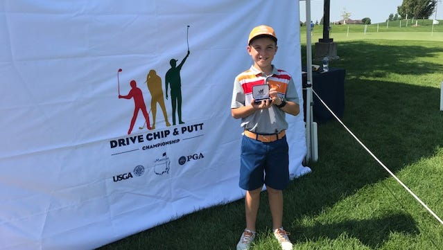 Clearwater's Luke Ashbrook holding a prize for a strong performance in a putting competition in Fargo.