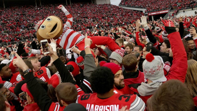 Brutus the Buckeye, Ohio State's mascot, is lifted into the air by Ohio State fans after thousands of them swarmed the field celebrating their team's win in two overtimes, 30-27, over Michigan at Ohio Stadium on Saturday, Nov. 26, 2016.