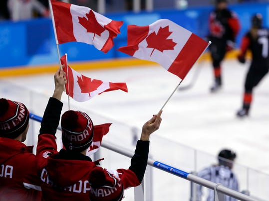Fans wave flags during the third period of the preliminary round of the women's hockey game between Canada and Finland at the 2018 Winter Olympics in Gangneung, South Korea, Tuesday, Feb. 13, 2018. (AP Photo/Frank Franklin II)