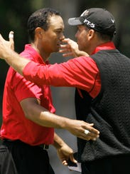 Tiger Woods, left, hugs Rocco Mediate following his