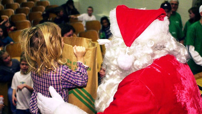 In this 1999 Gleaner file photo, Santa hands out bags of toys to 625 children attending the Goodfellows Christmas party at the South Junior High auditorium.