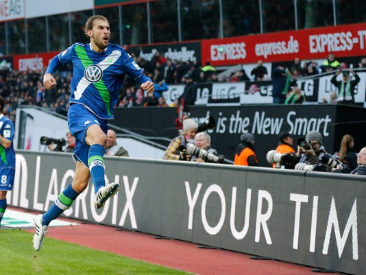 Wolfsburg's Bas Dost from the Netherlands celebrates scoring his sides fifth goal during the German first division Bundesliga soccer match between Bayer Leverkusen and VfL Wolfsburg in Leverkusen, Germany, Saturday, Feb. 14, 2015. (AP Photo/Frank Augstein)