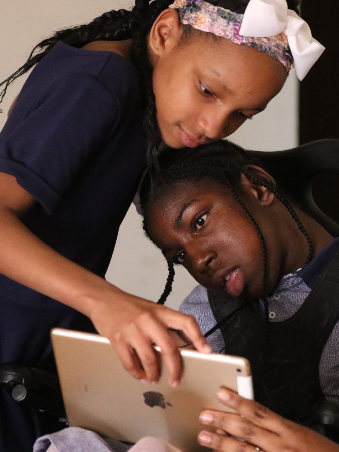 Sister Tailiyah Rush holds a computer tablet for Tochmirra