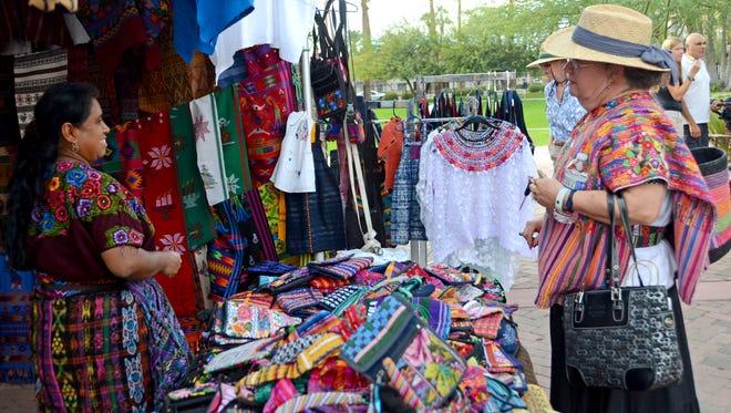 Emma Benavides (right) talks to Mariquita Santos, a vendor selling colorful clothing and bags from Ecuador at a past Spanish Market: Mercado de las Artes at the Heard Museum.