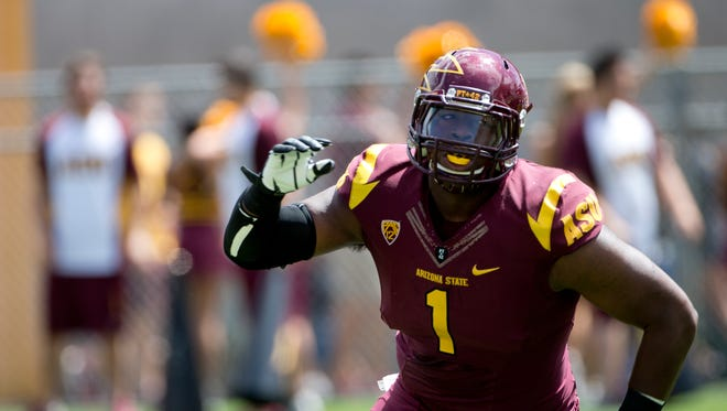 ASU DL Marcus Hardison looks to block during a gold vs. maroon game at Sun Devil Stadium during Fanfest on April 19,2014. Fans had their photo taken with Sparky, autographs with player and watched a gold vs. maroon game.