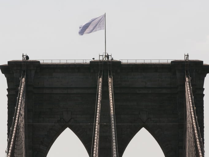 New York City Police officers stand at the base of a white flag flying atop the west tower of the Brooklyn Bridge, Tuesday, July 22, 2014. Two large American flags atop the Brooklyn Bridge were replaced sometime during the night with white banners. Police crime scene and intelligence detectives were investigating how the flags were switched out on the famed span that connects Brooklyn and Manhattan, and there were no reports of suspicious activity, police said. (AP Photo/Richard Drew)