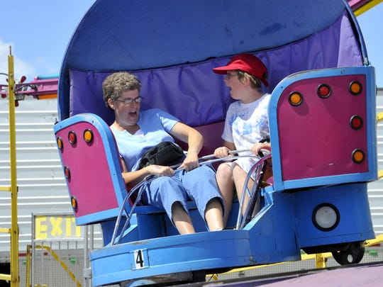 "Deb Heimbigner and her daughter Kristin ride the ""Super Tilt"" at the Four County Fair in Shelby."