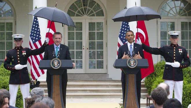 US President Barack Obama and Turkish Prime Minister Recep Erdogan hold a joint press conference during a rain shower, in the Rose Garden of the White House in Washington, DC, May 16, 2013.
