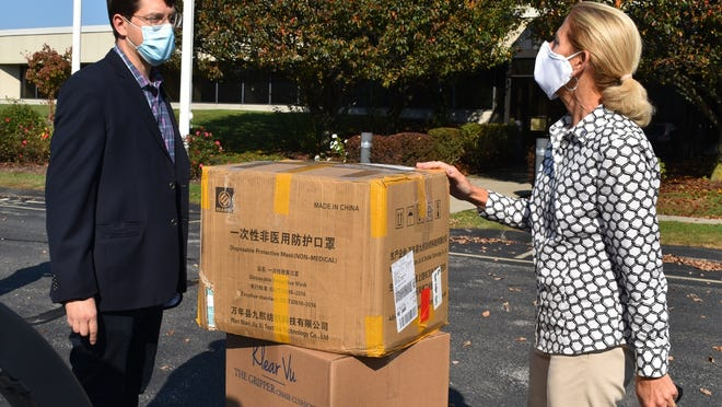 Klear Vu president Ben Cooper and state  Rep. Carole Fiola load up boxes of masks to be donated.