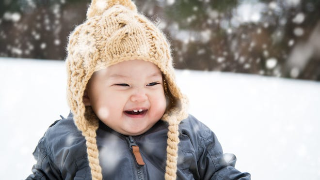 Close up of a baby wearing a hat and jacket playing outside in the snow, and laughing. Tottori, Japan. January 2016