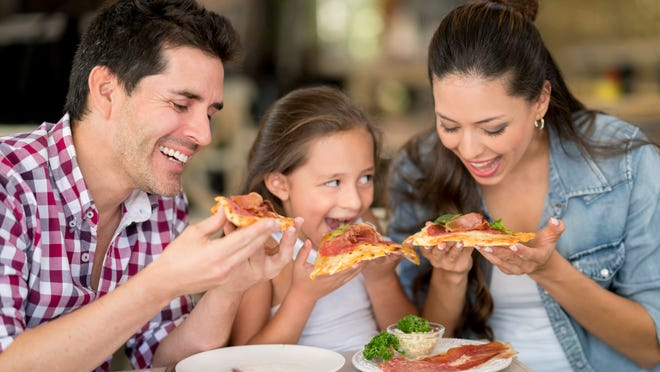 Happy Latin American family eating pizza at a restaurant - food and drinks concepts
