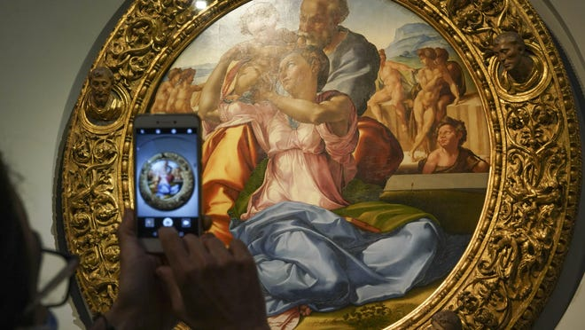 """A member of the media takes a picture of 15th century painting """"Doni Tondo"""" by Michelangelo Buonarroti, during a press tour of the Uffizi museum on the day off its reopening, in Florence, Wednesday, June 3, 2020. The Uffizi museum reopened to the public after over two months of closure due to coronavirus restrictions."""