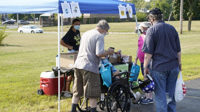 Kristi Carlson, a HOPE program facilitator, passes out snacks and drinks on Wednesday at the HOPE Community Center in Adrian. HOPE staff hosted a parking lot party on Wednesday as a way to reconnect with members who have been stuck at home during the pandemic.