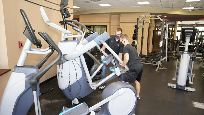 Jeff Tyson, operations director, and Evan Platonas, fitness director, move fitness machines Friday at the Christian Family Centre's co-ed fitness area to provide for 6 feet of separation. The facility is set to reopen Wednesday, Sept. 9.