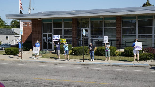 A group of protesters stand in front of the Adrian Post Office, 143 E. Maumee St., Saturday in support for the United States Postal Service. Similar rallies took place in Blissfield and Tecumseh.
