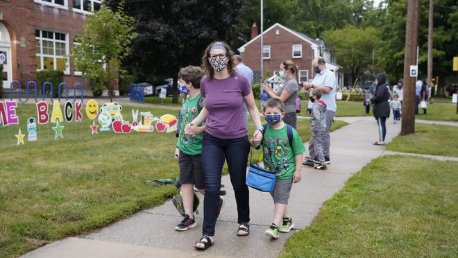 Elly Sager walks her boys Alex, fourth grade, and Nico, kindergarten, to their first day of school on Tuesday at Lincoln Elementary. Tuesday was the first day of in-person instruction at Adrian Public Schools since March.