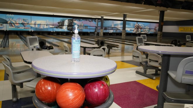A bottle of hand sanitizer sits atop a rack of bowling balls Friday afternoon inside the Lenawee Recreation Center, 520 College Ave., Adrian. In Gov. Gretchen Whitmer's latest order Thursday, bowling alleys can open for organized competitions.