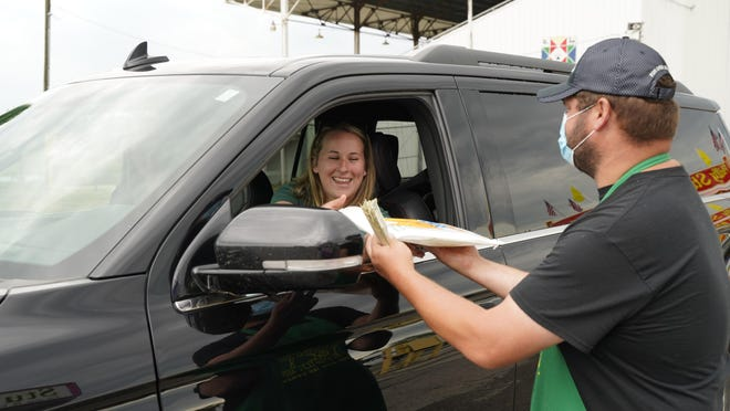 Adriane Bernotas of Hudson gets an elephant ear from Mike Campbell July 10 at the Lenawee County Fair and Event Grounds during a fair food drive-thru. The fair board is hosting its second drive-thru Saturday and Sunday, Sept. 26-27.