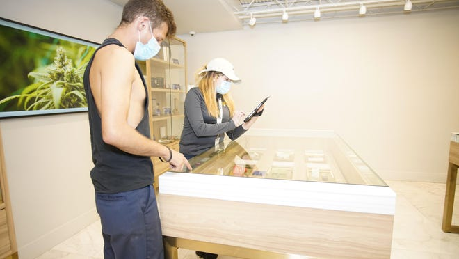 Lume Cannabis Co. employee Lauren Corba assists customer Chad Smith of Adrian in selecting some marijuana Friday at the Adrian dispensary.