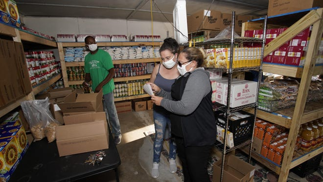 City of Refuge Ministries International Pastor De'Angelo Boone, left, with Teresa Tuttle and administrator Jennifer Carter pack food supplies for families on Friday. The church at 301 S. Tecumseh St. in Adrian launched a food pantry in March.