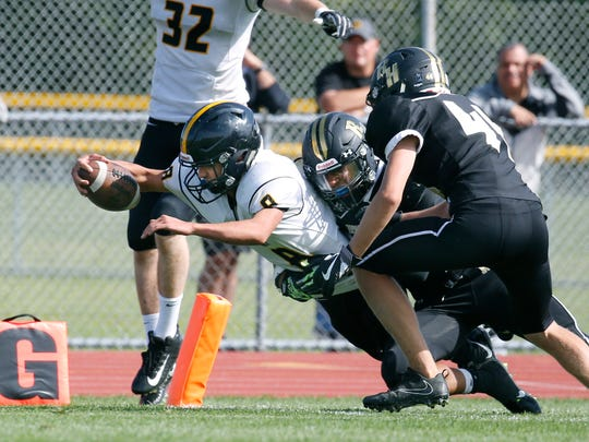 Rush-Henrietta's Rayshod Walker attempts to tackle McQuaid's AJ Fina near the goal line during a game last season