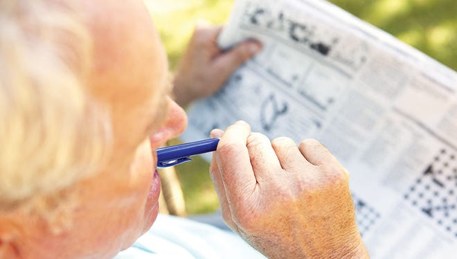 Elderly man working on a crossword puzzle