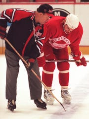 Red Wings coach Scotty Bowman shows Sergei Fedorov something with the stick during practice at Joe Louis Arena on April 17, 1997.