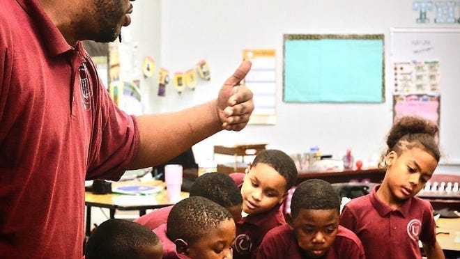 Devin Dykes, a social studies teacher at the Texas Empowerment Academy, talks with students in the school's chess club in December 2019. The club practiced new strategies before the 2019 Texas Charter School Academic & Athletic League Regional Chess Competition. Photo courtesy of Texas Empowerment Academy.