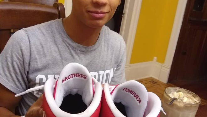 Jakoby McKown is transferring from Brimfield High School to Bellevue, Neb., so he can play basketball this winter. Here, he holds some special-order shoes to honor the memory of his best friend and teammate, Aaron Miller, who died in a car crash over the summer.