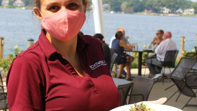 A member of the waitstaff at Boatwerks Waterfront Restaurant poses with an entree while wearing gloves and a mask. The recent wave of COVID cases has led to increased struggles at local restaurants.
