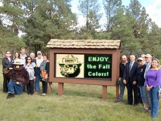 Joining Smokey Bear for the dedication of a new LED sign at his ranger district in Ruidoso are from left. Marci Butchofsky, Cindi and Riker Davis, Mary Parra, Rick Merrick, Leroy Cockrell, Mary Weaver, Dave Warnack, Richard Hall, Daryl Lindsay, Mary Ann Russ, Roger Allen and Jeannette Sessuns.