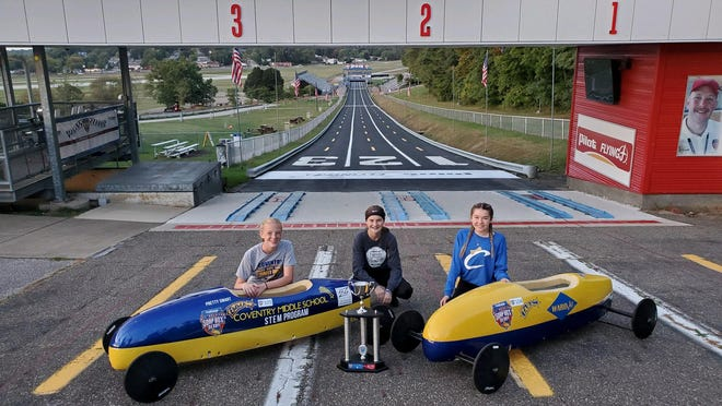 Coventry High School students pose next to their winning Super Stock derby car. Coventry, Springfield and Green are apart of the International Soap Box Derby's Gravity Racing Challenge.