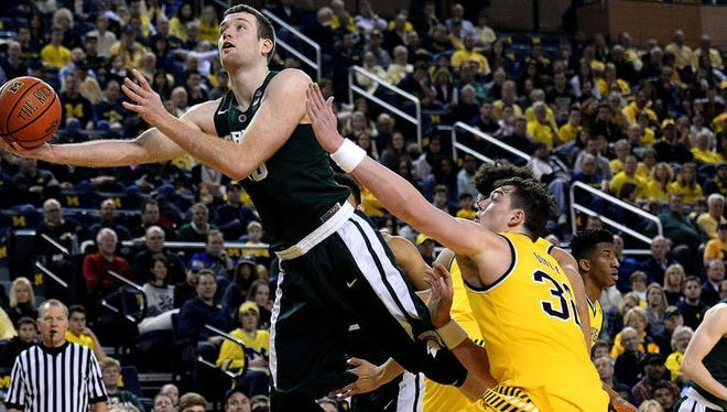 MSU's Matt Costello goes up for an off-balance shot in the second half of MSU's 89-73 victory over Michigan Saturday at Crisler Center in Ann Arbor.