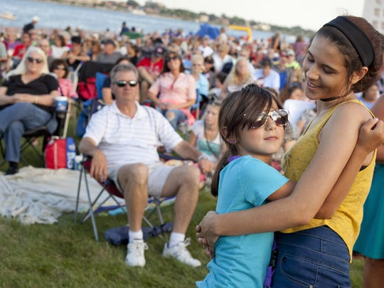 Sisters Kayla Olvera, 17, and Zoe Danna, 7, dance together during Rockin' the Rivers Thursday at Kiefer Park in Port Huron.