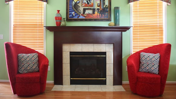 A pair of asymmetrical chairs flank the fireplace in