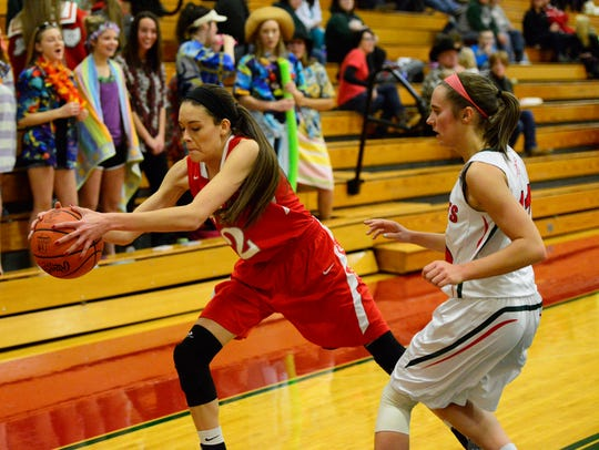 SJCC's Adrienne Wehring saves the ball off Oak Harbor defender Abby Dornbusch.