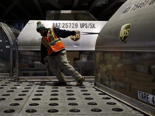 A UPS worker pulls a container full of packages across