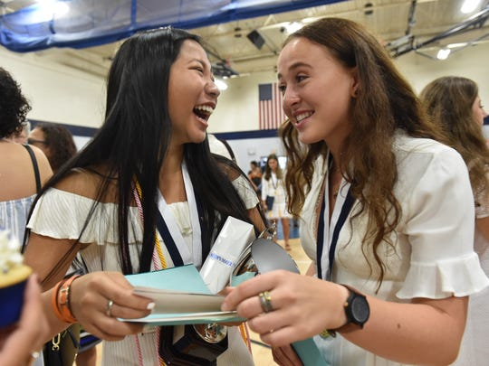 Teana Tee (left) and Clara Masseau laugh over old photos of themselves in first grade while celebrating after their St. Edward's School class of 2018 commencement ceremony at the Waxlax Center for the Performing Arts on Saturday, May 26, 2018, in Vero Beach.