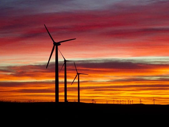 The rising sun outlines turbines turning in a stiff