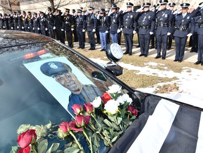 Police officers from across Michigan and beyond stand