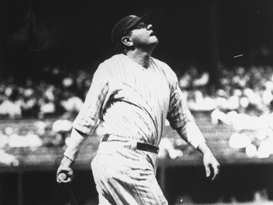Babe Ruth is shown lofting another home run into the