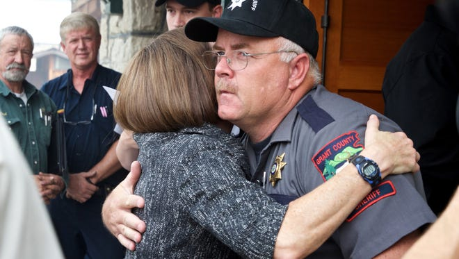 In this Aug. 19, 2015 file photo, Oregon Gov. Kate Brown hugs Grant County Sheriff Glenn Palmer as they enter a meeting with homeowners in Canyon City.