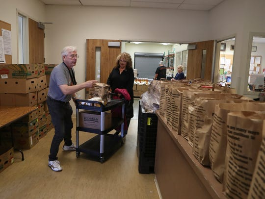 Dee McDaniel, right, picks up food from the food bank