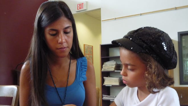 During a 2010 summer reading camp at St. Thomas Aquinas College in Sparkill, student teacher Orietta Osso helps camper Sofia Ceparano of Pearl River read flashcards.