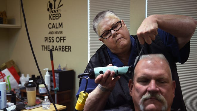 Dee Johnson, owner of Old West Barber, gives Bill Grigg a haircut in Reno on July 29, 2016.