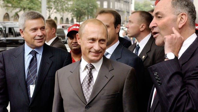 Russian President Vladimir Putin, center, and Lukoil President Vagit Alekperov, left, listen as Sen. Chuck Schumer, D-N.Y., gestures as he speaks about U.S.-Russian relations during the opening of Lukoil's gasoline station on Sept. 26, 2003, in the Chelsea neighborhood of New York City.
